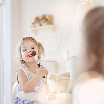 Маленькая девочка в комнате своей матери, используя макияж, чтобы подражать взрослым