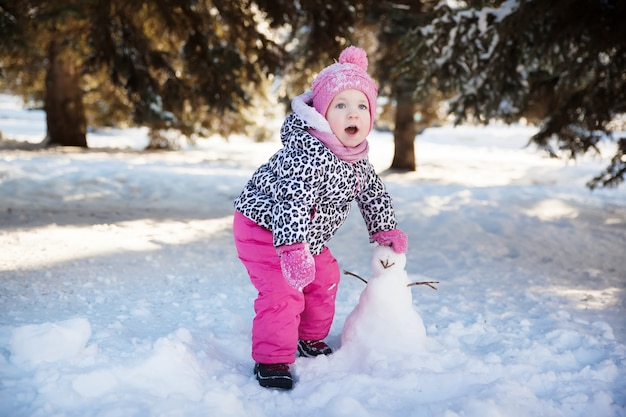 Маленькая девочка играет со снеговиком