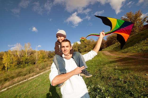 Отец с сыном осенью играет с кайтом