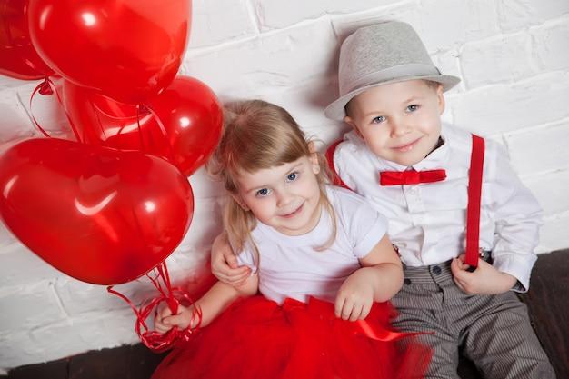 小さな子供たちを保持し、ハートの風船を拾います。バレンタインの日、白い背景の上の愛の概念