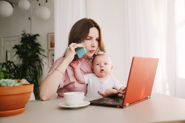 ママと赤ちゃん。ラップトップを操作し、電話で話している若い母親。