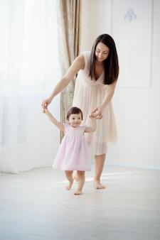 母と幼い娘が寝室で遊んで