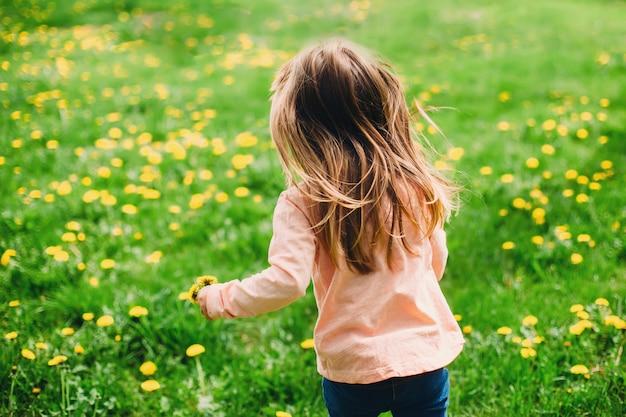 Маленькая девочка бежит по зеленой лужайке с жёлтыми одуванчиками