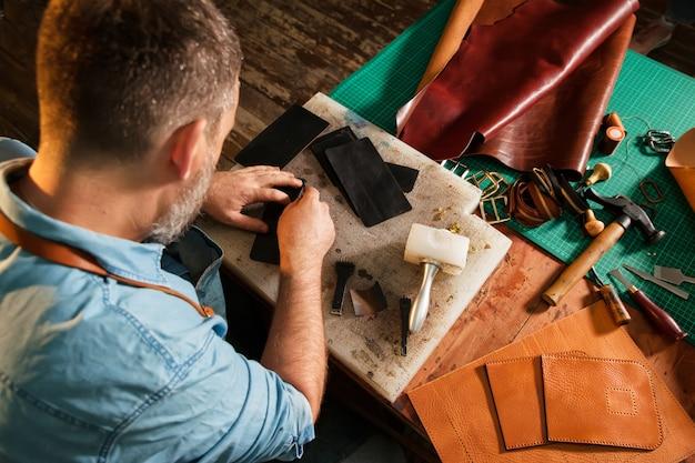 Человек, работающий с кожей, используя крафт-инструменты.