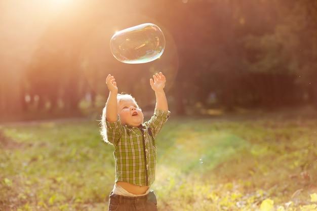 Маленький мальчик на закате ловит мыльные пузыри