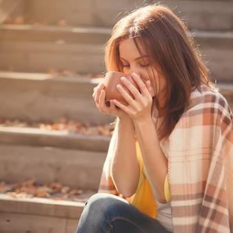 休憩とウールの格子縞の毛布に包まれた階段で秋の庭に座ってお茶を飲む若い女性