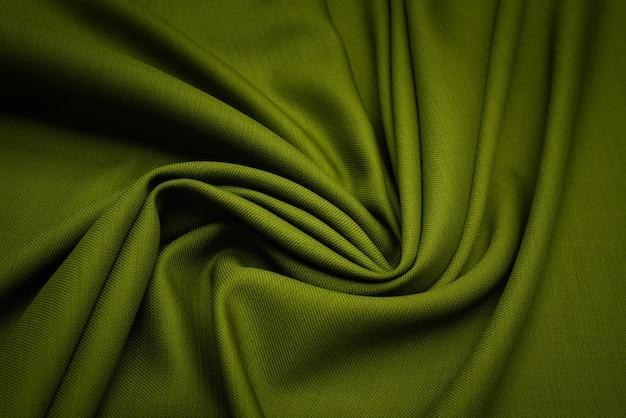 ウール生地のテクスチャは濃い緑色の背景です。