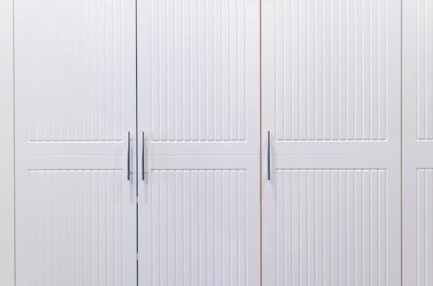 ホテルの部屋にある白いワードローブのドア