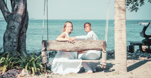 Красивая блондинка невеста в белом свадебном платье стоять на берегу моря. тропическое море и скалы на заднем плане. концепция летних каникул.