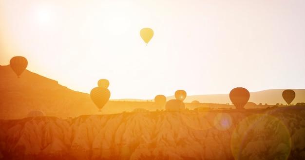 カッパドキアトルコの岩の風景の上を飛んでいる熱気球