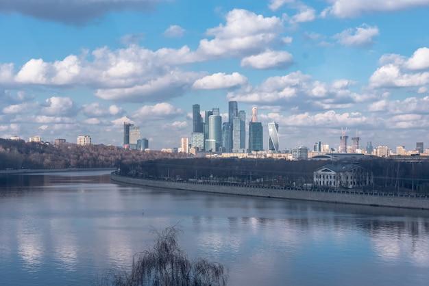 Международный финансовый и торговый центр москва сити в российской столице. гигантские металлические небоскребы под ярким солнцем. солнечный свет отражается на огромном здании.