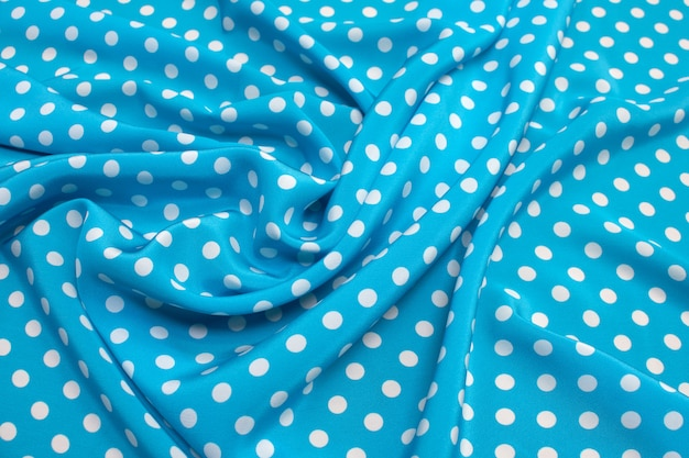 Текстура шелковой ткани с белым горошком на синем.