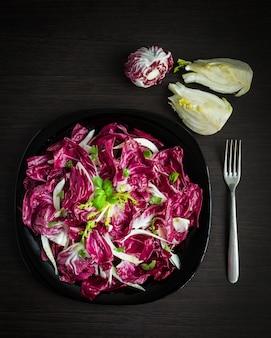 フェンネルと簡単ダイエットチコリサラダ。エンダイブ、新鮮でヘルシーな野菜サラダ。イタリアのベネチアンビターとスパイシーな味の赤チコリのラディッキオサラダ。ベジタリアンフード。健康食品。