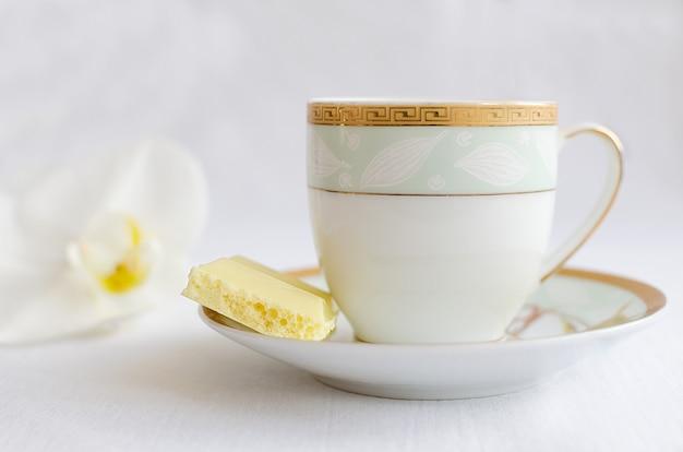 おいしい白い多孔質チョコレートとコーヒーカップ