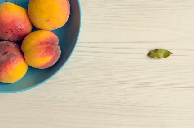 Спелые персики в синей миске