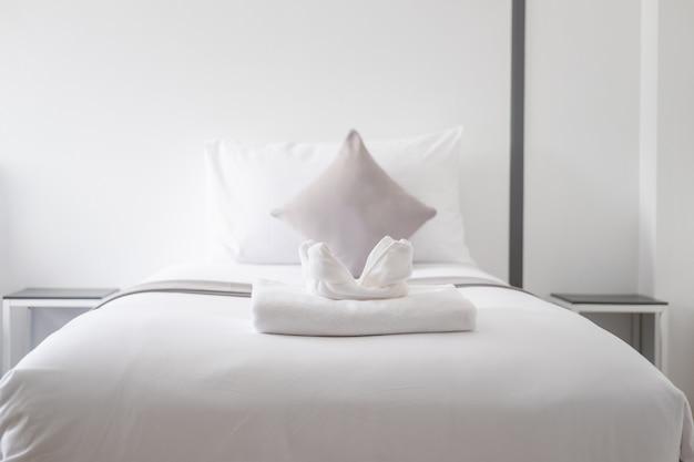 寝室のシングルベッドに白い新鮮なタオル