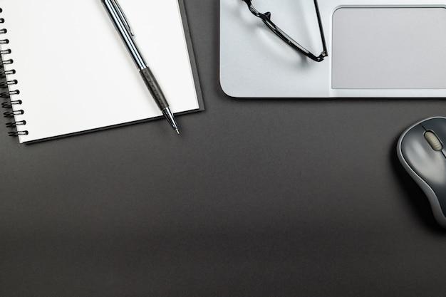 Вид сверху офисного стола с блокнотом ручкой и ноутбуком