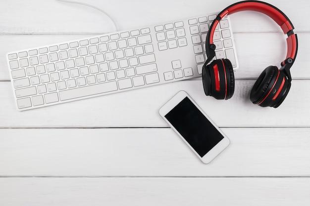 Вид сверху мобильного телефона и клавиатуры наушников