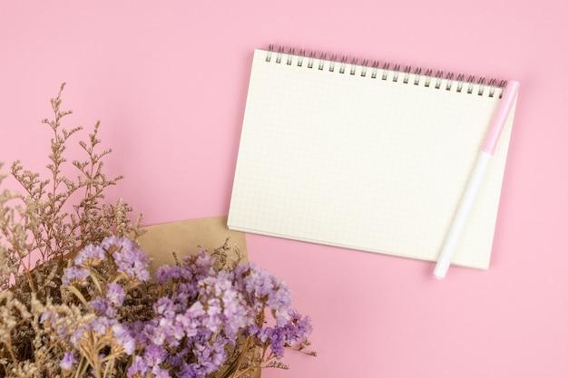 Вид сверху пустой блокнот и букет цветов на пастельно-розовом столе