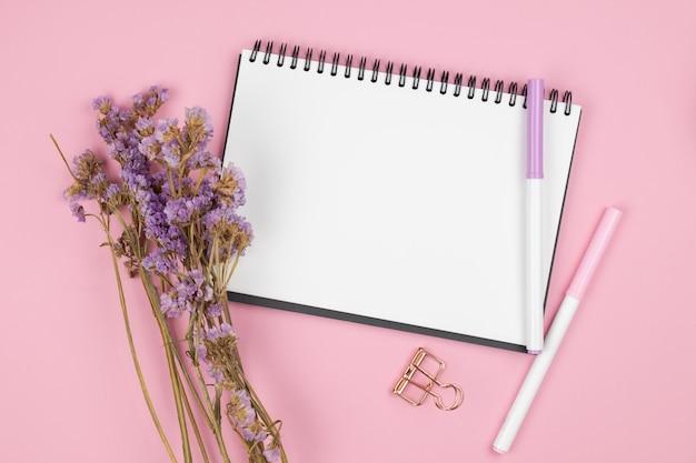 Вид сверху ноутбука и фиолетовый цветок на розовом столе
