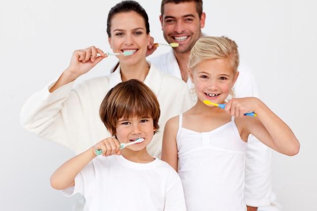 Портрет семьи, убирающей зубы в ванной комнате