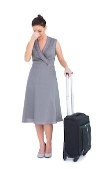 頭が痛むスーツケース付きのゴージャスな女性