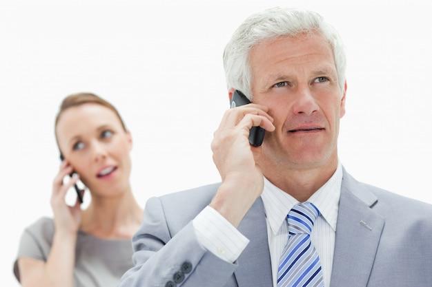 白い髪のビジネスマンのクローズアップは、女性と電話で話す