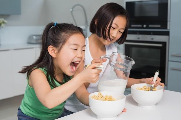 キッチンで穀物を食べる幸せな若い女の子