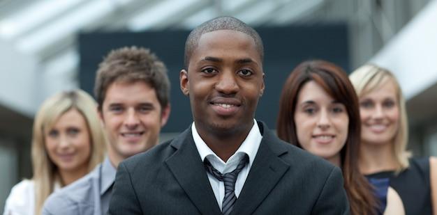彼のチームと一緒にカメラで笑っているアフロアメリカ人の実業家