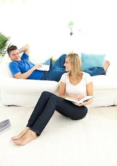 リビングルームで幸せなカップルの読書