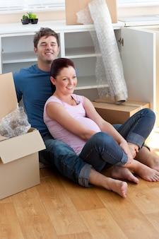 若い未来の両親が段ボールに囲まれた床に座っている