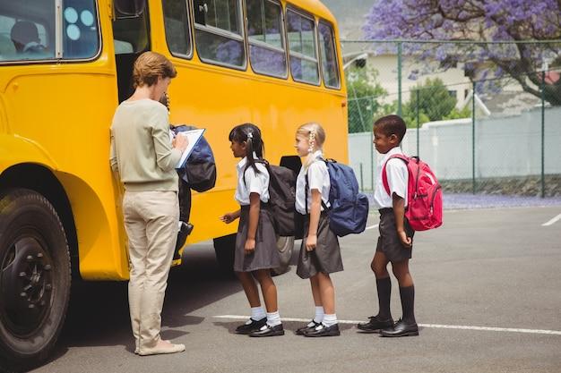 Симпатичные школьники ждут, чтобы попасть в школьный автобус