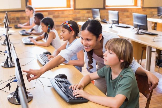 Симпатичные ученики в компьютерном классе с учителем