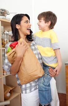 Симпатичный маленький мальчик, распаковывающий продуктовый портфель с матерью