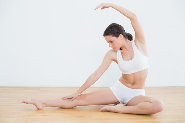 フィットネススタジオで手と脚を伸ばしトーン女性