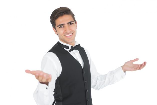 ハンサムな若いウェイターは、特定のジェスチャーを作る