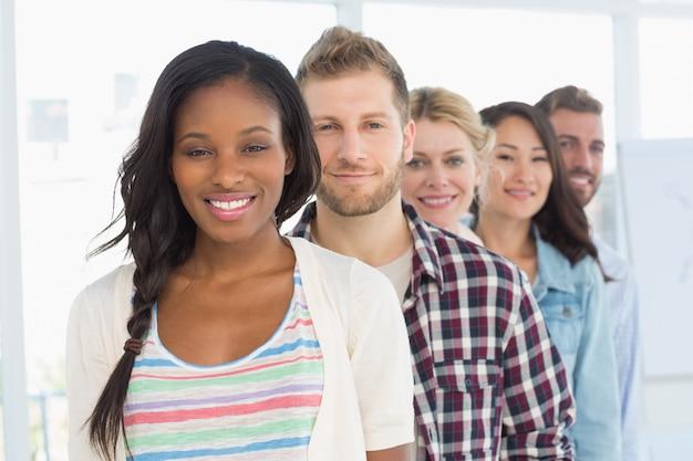 Разнообразная команда разработчиков, стоящая в очереди, улыбаясь на камеру