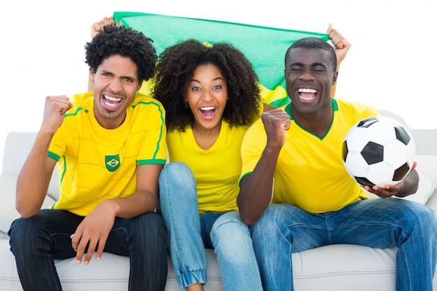 ブラジルの旗でソファに座っている黄色の興奮したサッカーファン