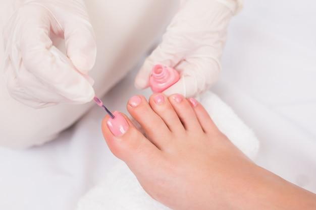 彼女の足の指先を塗っている女性