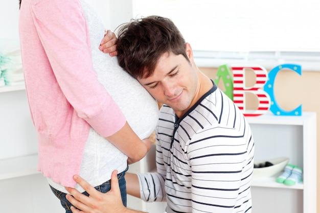 Крупный план прекрасный человек с головой на живот беременной женщины