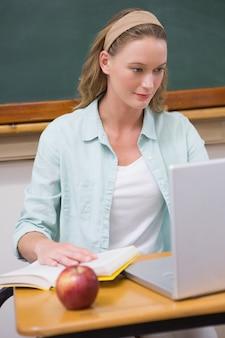 彼女の机の上に集中する先生