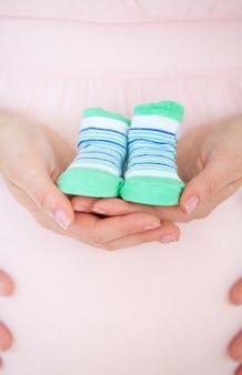 Крупным планом кавказской беременной женщины с детской обуви и ее мужа