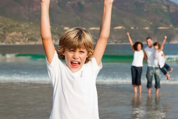 Маленький мальчик на пляже с родителями и его сестрой в фоновом режиме