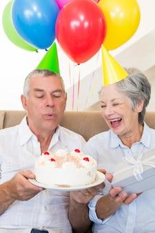 誕生日を祝うソファに座っているシニアカップル
