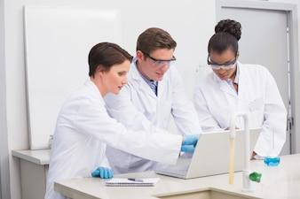 ラップトップと一緒に働く集中した科学者