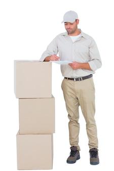 Человек доставки, пишущий в буфере обмена, стоя на стойках