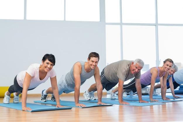 Группа делает отжимания в ряду в классе йоги