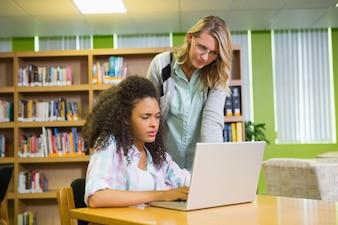 Студент получает помощь от преподавателя в библиотеке
