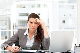 ラップトップとフォルダーで彼女の机で働く心配している実業家