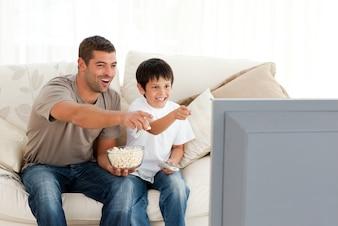 ポップコーンを食べながら幸せな父と息子がテレビを見て